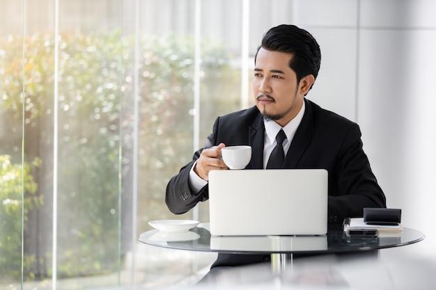 Uomo di affari che lavora con il computer portatile e che beve una tazza di caffè