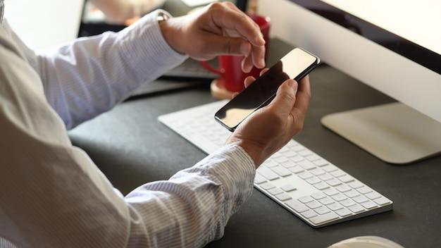 Uomo di affari che lavora con il telefono cellulare in ufficio