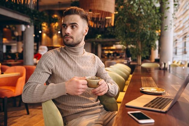 Uomo di affari che lavora su un computer in un caffè