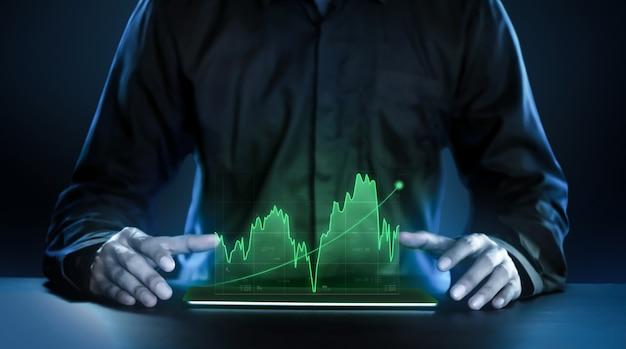 Uomo di affari che mostra i grafici proficui di tecnologia olografica del mercato azionario