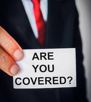 Uomo di affari che mostra i testi del concetto di assicurazione