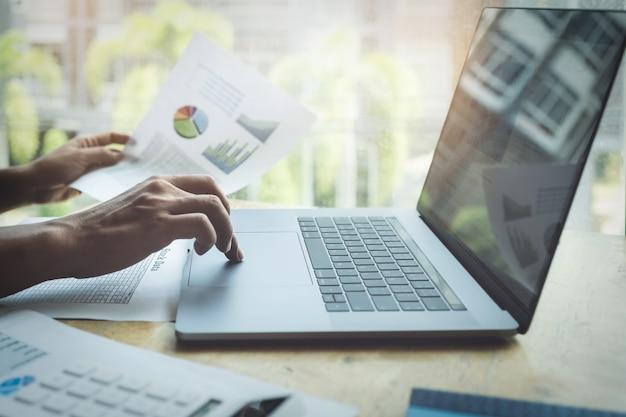 Uomo di affari che per mezzo del calcolatore per esaminare annuale del bilancio con per mezzo del computer portatile per calcolare il preventivo.