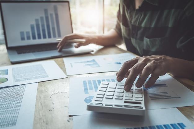Uomo di affari che per mezzo del calcolatore per rivedere il bilancio annuale con la penna di tenuta e per mezzo del computer portatile al bilancio calcolatore. verifica e verifica dell'integrità prima del concetto di investimento.