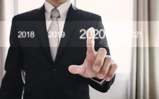 Uomo di affari che preme sul 2020, concetto di nuovo anno
