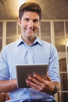 Uomo di affari che propone con il suo tablet