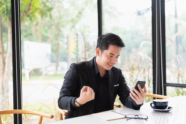 Uomo di affari che sembra il cellulare e felice