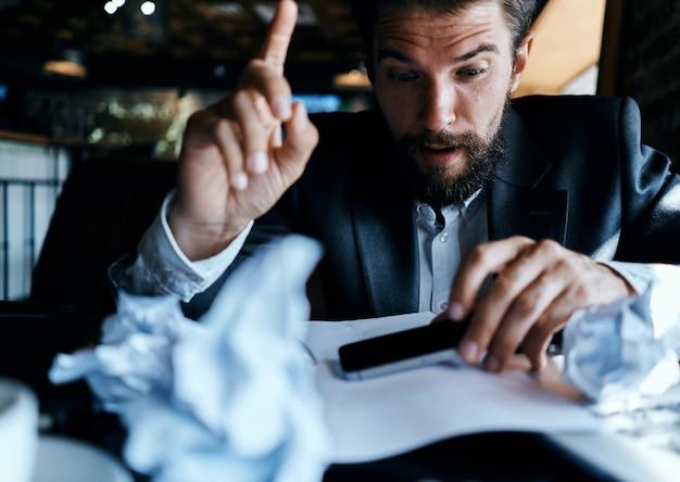 Uomo di affari che si siede al tavolo davanti alla tecnologia del lavoro esecutivo di carta stropicciata laptop lifestyle