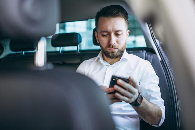 Uomo di affari che si siede in un'automobile facendo uso del telefono
