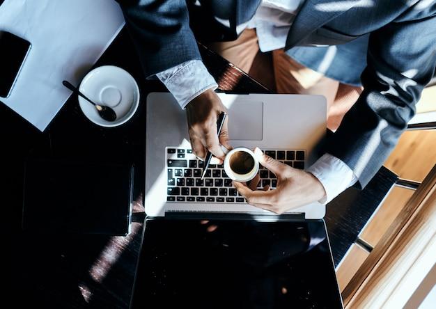 Uomo di affari che si siede in un caffè davanti a uno stile di vita di tecnologia di vista superiore esecutiva della tazza di caffè dei documenti del computer portatile. foto di alta qualità