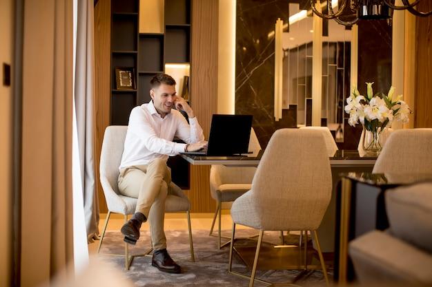Uomo di affari che si siede in una stanza lussuosa davanti ad un computer portatile