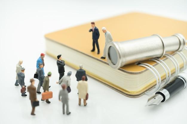 Uomo di affari che sta sul libro con il binocolo facendo uso come concetto del reclutatore di lavoro di affari.