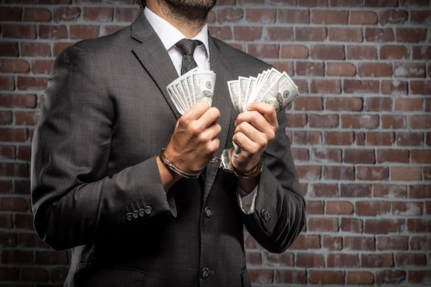 Uomo di affari che tiene le fatture di denaro con una manetta in una prigione. concetto di corruzione, politici corrotti, attività illegali. sfondo di mattoni.