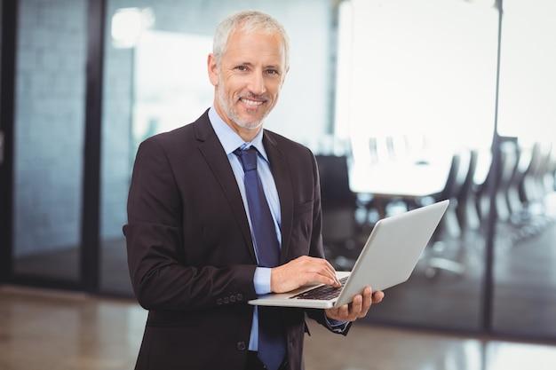 Uomo di affari che utilizza computer portatile nell'ufficio