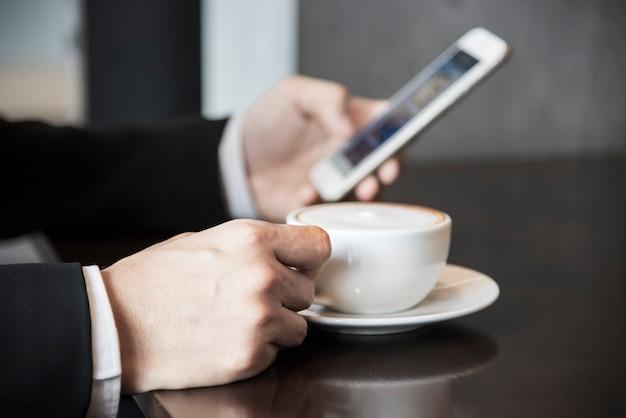 Uomo di affari che utilizza telefono cellulare mentre bevendo caffè in caffetteria