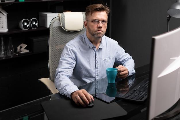 Uomo di affari con i vetri che lavora nell'ufficio alla tavola del computer e che beve caffè dalla tazza luminosa