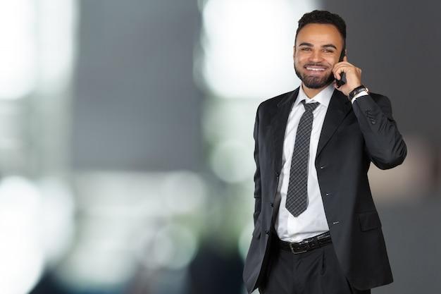 Uomo di affari dell'afroamericano che per mezzo del telefono mobile