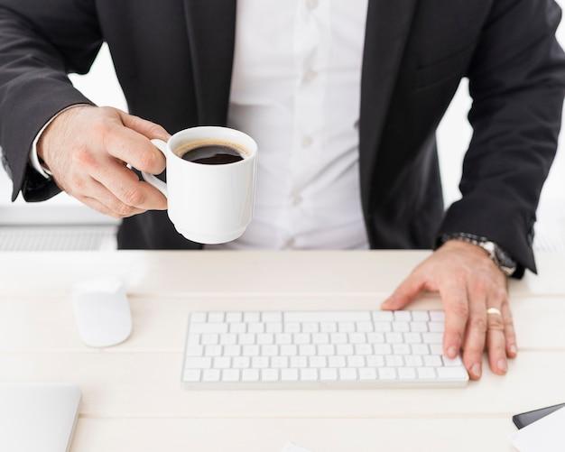 Uomo di affari dell'angolo alto che gode di una tazza di caffè