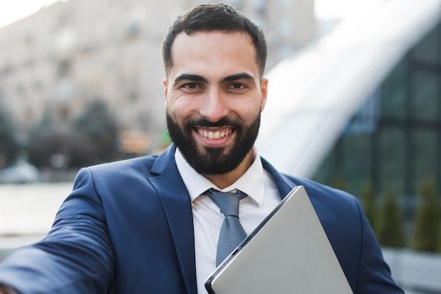 Uomo di affari dell'angolo alto con il computer portatile