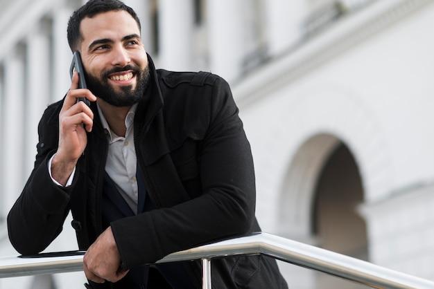 Uomo di affari di angolo basso che parla sopra il telefono
