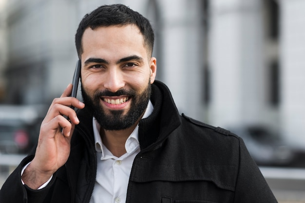Uomo di affari di vista frontale che parla al telefono