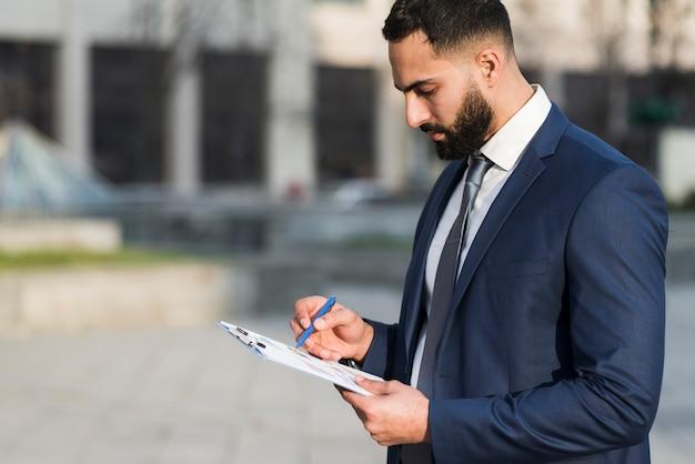 Uomo di affari di vista laterale che controlla lavagna per appunti