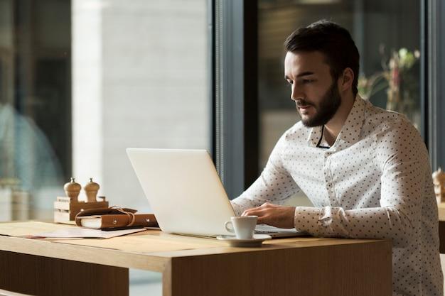 Uomo di affari di vista laterale che lavora al computer portatile