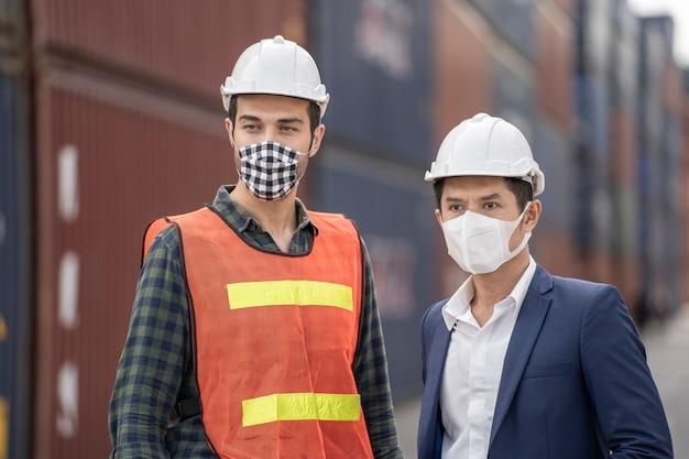 Uomo di affari e operai che indossano in una maschera medica e un panno di sicurezza al magazzino del carico all'aperto della fabbrica.