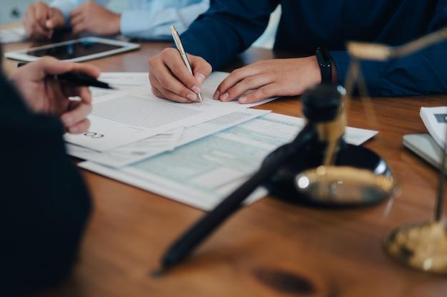 Uomo di affari e squadra e avvocati che discutono le carte del contratto con scala d'ottone sullo scrittorio di legno in ufficio. legge, servizi legali, consulenza, concetto di giustizia.