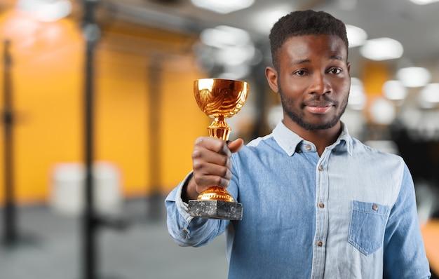 Uomo di affari felice che tiene un trofeo