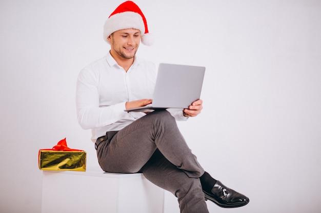 Uomo di affari in cappello della santa che compera online su natale