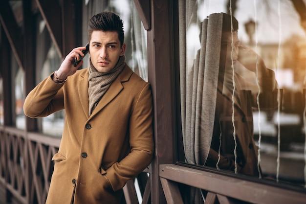 Uomo di affari in cappotto che comunica sul telefono all'esterno