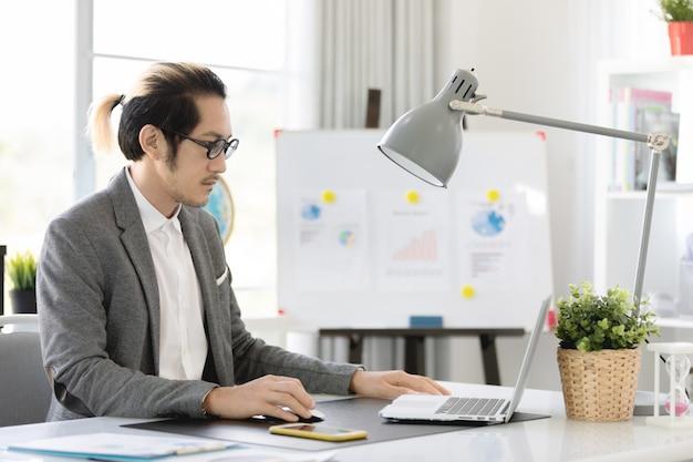 Uomo di affari in ufficio per mezzo del computer portatile e del telefono cellulare