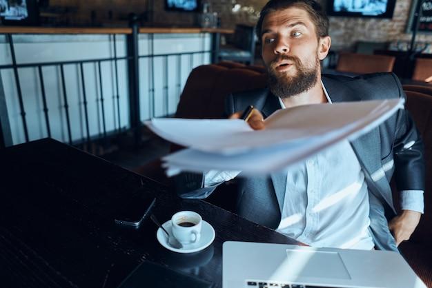 Uomo di affari in un vestito del caffè davanti alla tecnologia dei documenti ufficiali di emozioni del computer portatile.