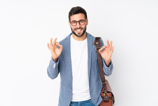 Uomo di affari isolato sulla parete bianca che mostra un segno giusto con le dita