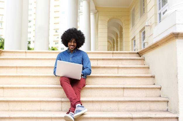 Uomo di afro che si siede sui punti per mezzo del computer portatile