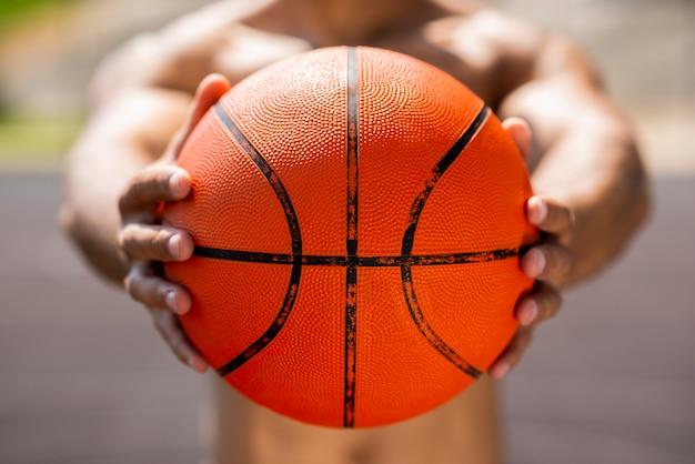 Uomo di afro che tiene una palla di pallacanestro