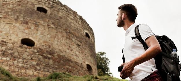 Uomo di angolo basso che esamina castello