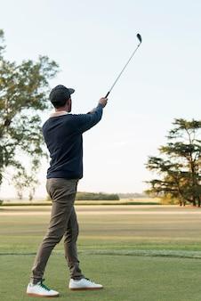 Uomo di angolo basso che gioca a golf