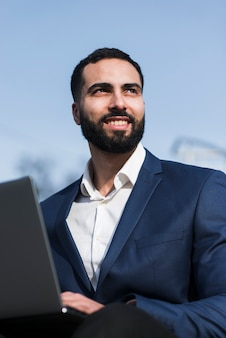 Uomo di angolo basso che lavora al computer portatile