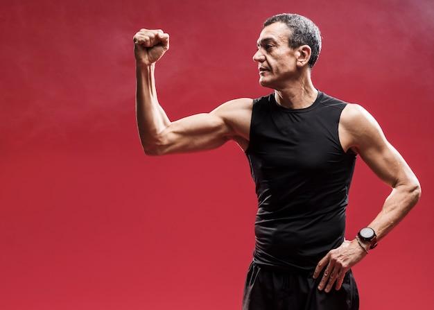 Uomo di angolo basso che mostra i suoi muscoli
