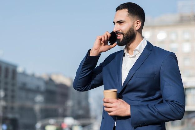 Uomo di angolo basso che parla sopra il telefono