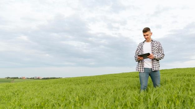 Uomo di angolo basso con la compressa all'azienda agricola