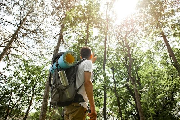 Uomo di angolo basso con lo zaino in foresta