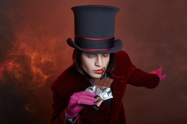 Uomo di circo favoloso in un cappello e un abito rosso in posa nel fumo su un buio