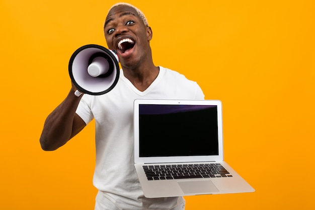 Uomo di colore africano con capelli bianchi con un megafono e un computer portatile con un modello su uno studio giallo
