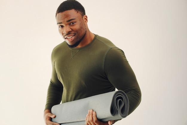 Uomo di colore bello che fa yoga su una parete bianca