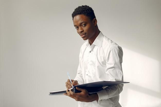 Uomo di colore bello che sta su una parete bianca