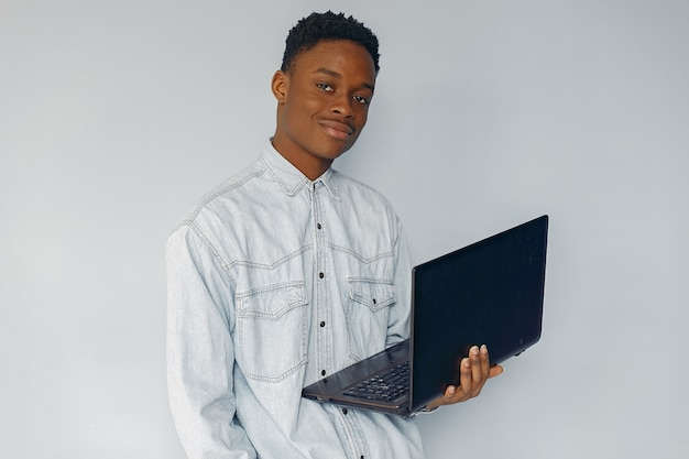 Uomo di colore bello che sta su una parete blu