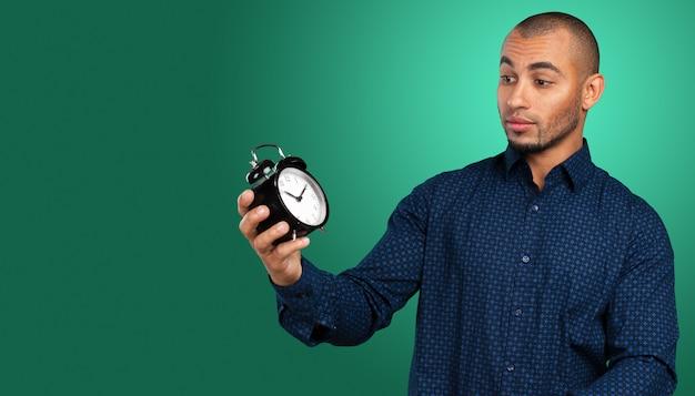 Uomo di colore bello che tiene orologio d'annata