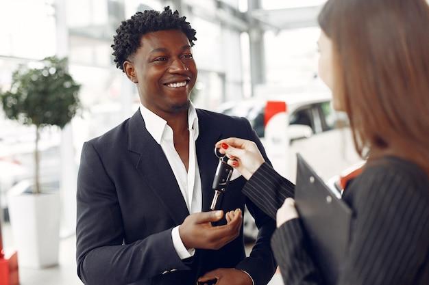 Uomo di colore bello ed elegante in un salone dell'automobile